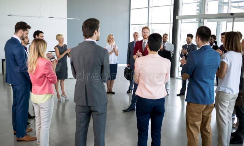 站立在他的伙伴前面的领导鼓掌 免版税库存照片