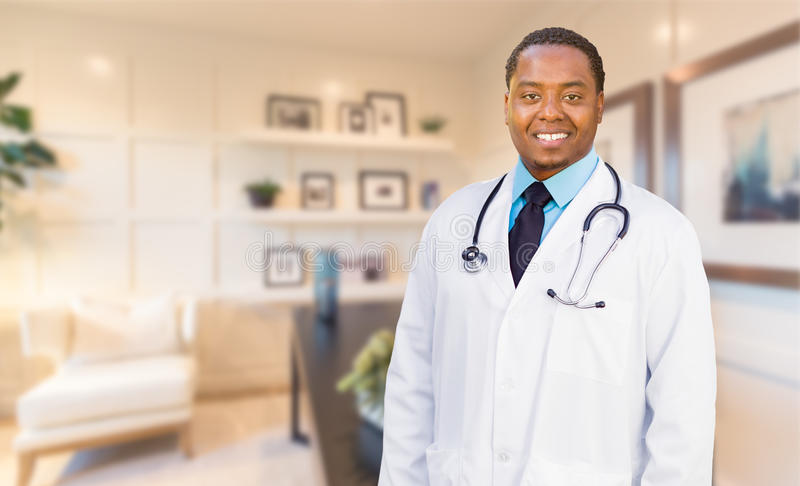 站立在他的办公室的年轻非裔美国人的医生或护士 图库摄影