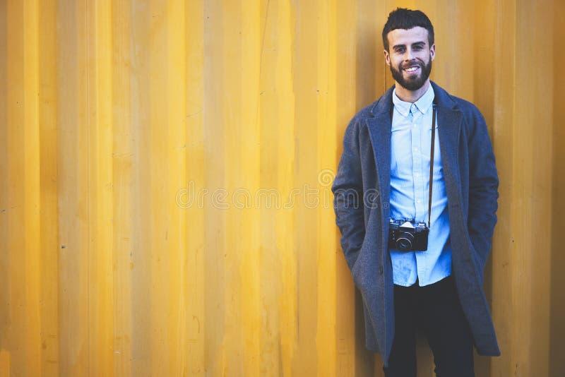 站立在他的博克的五颜六色的设置背景的牛仔布夹克的年轻行家博客作者旅客,当时 库存照片