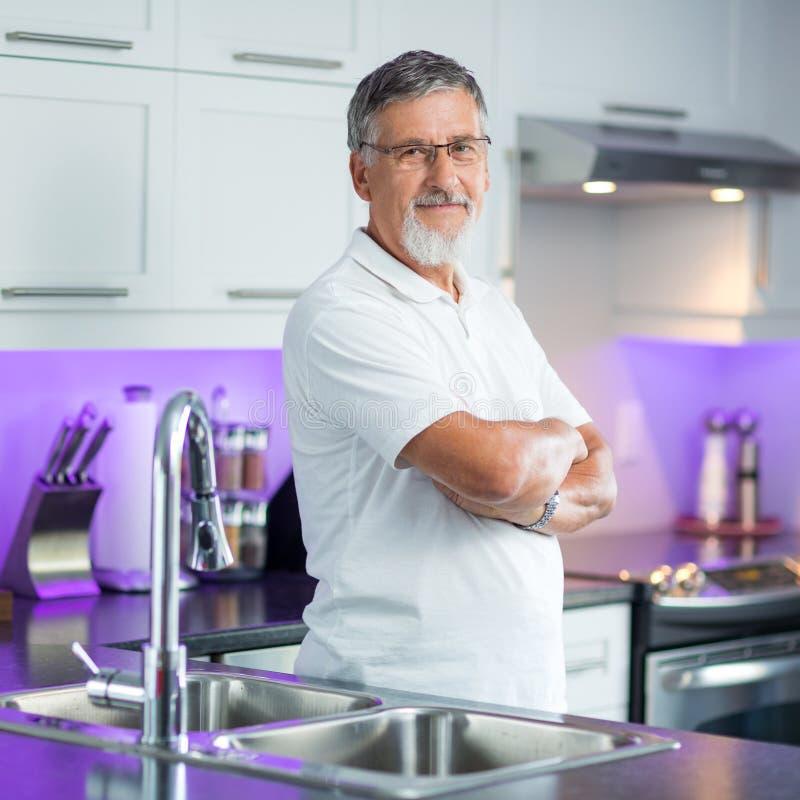 站立在他的厨房里的老人 免版税库存照片