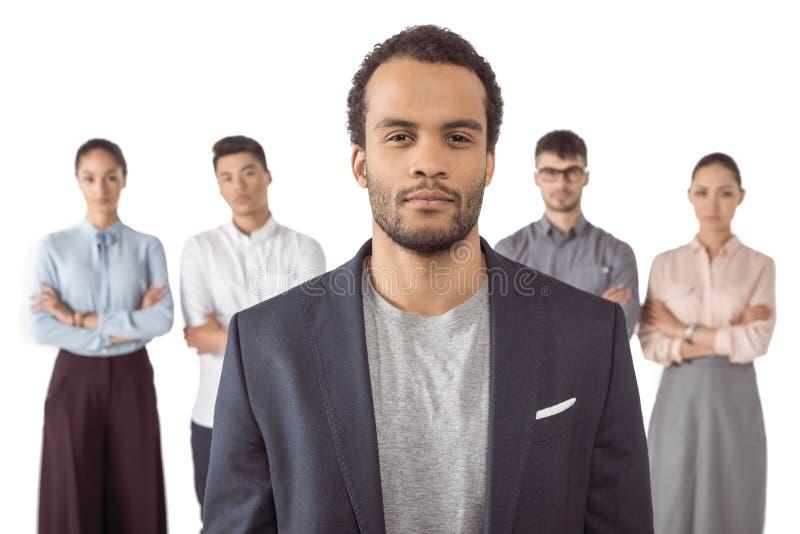 站立在他的同事前面的美国黑人的商人画象 免版税库存图片