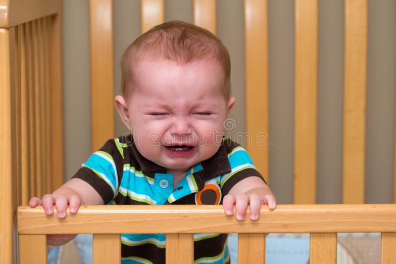 站立在他的小儿床的哭泣的婴孩 库存图片