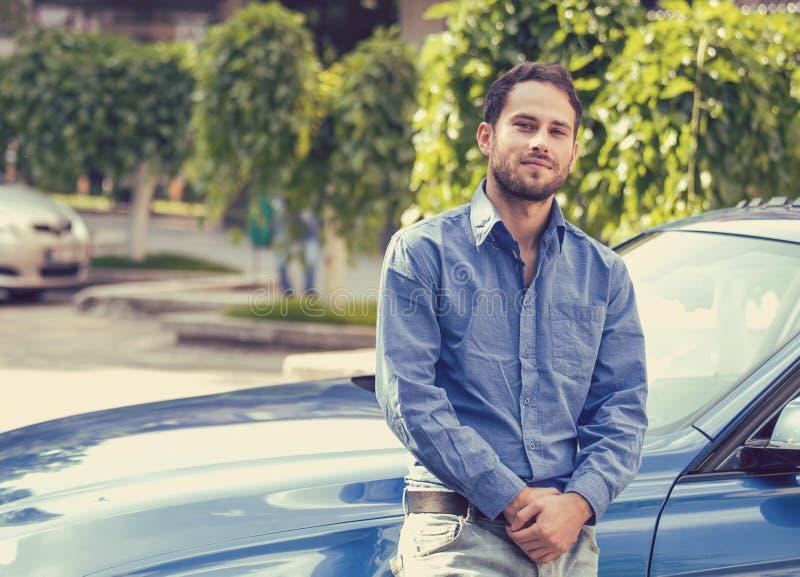 站立在他的汽车前面的英俊的人 免版税库存图片