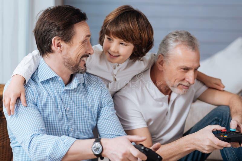 站立在他的父亲和祖父后的逗人喜爱的正面男孩 免版税库存图片