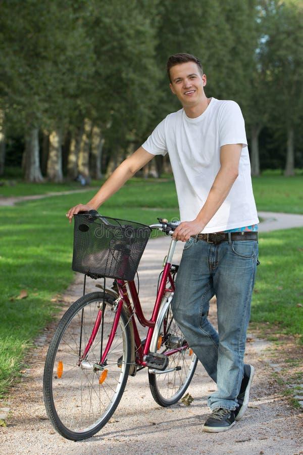 站立在他的自行车旁边的年轻人 库存照片