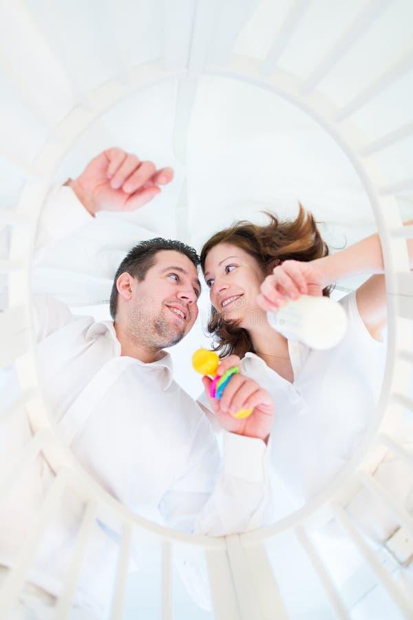 站立在他们的婴孩婴孩床的愉快的年轻父母  免版税库存照片