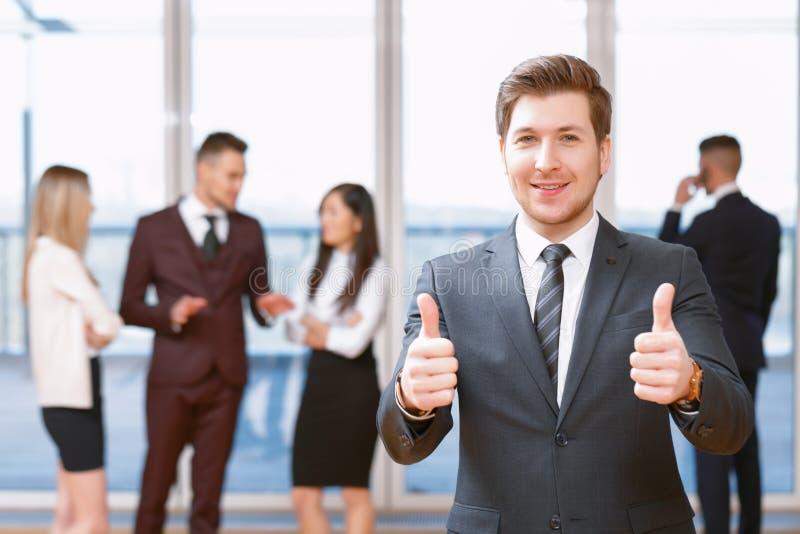 站立在他的co前面的年轻商人 免版税库存图片