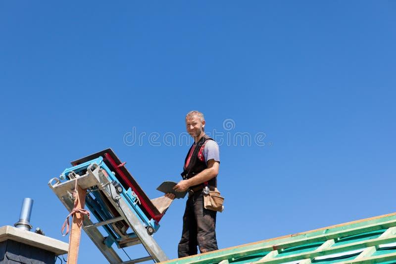 站立在建筑电梯附近的盖屋顶的人 免版税库存照片