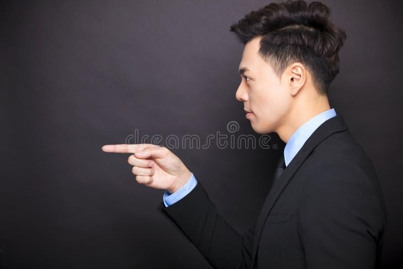站立在黑背景前的恼怒的商人 免版税库存照片