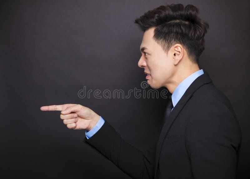 站立在黑背景前的恼怒的商人 免版税图库摄影