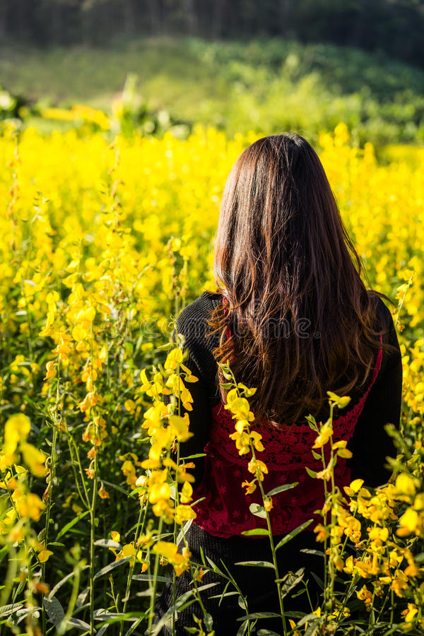 站立在黄色花园里的妇女, 免版税库存照片