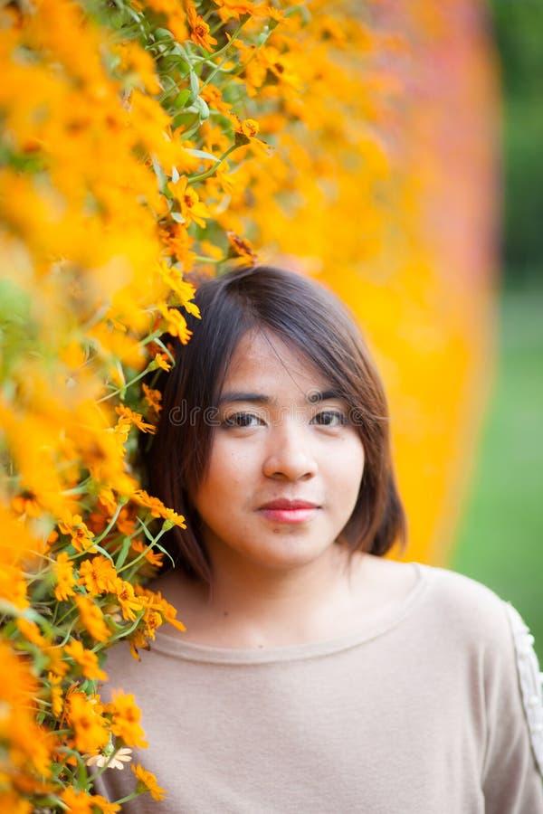 站立在黄色花附近的画象亚裔妇女。 免版税图库摄影