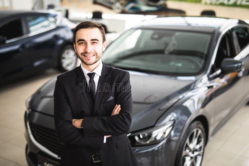 站立在经销权的英俊的年轻经典汽车推销员 图库摄影