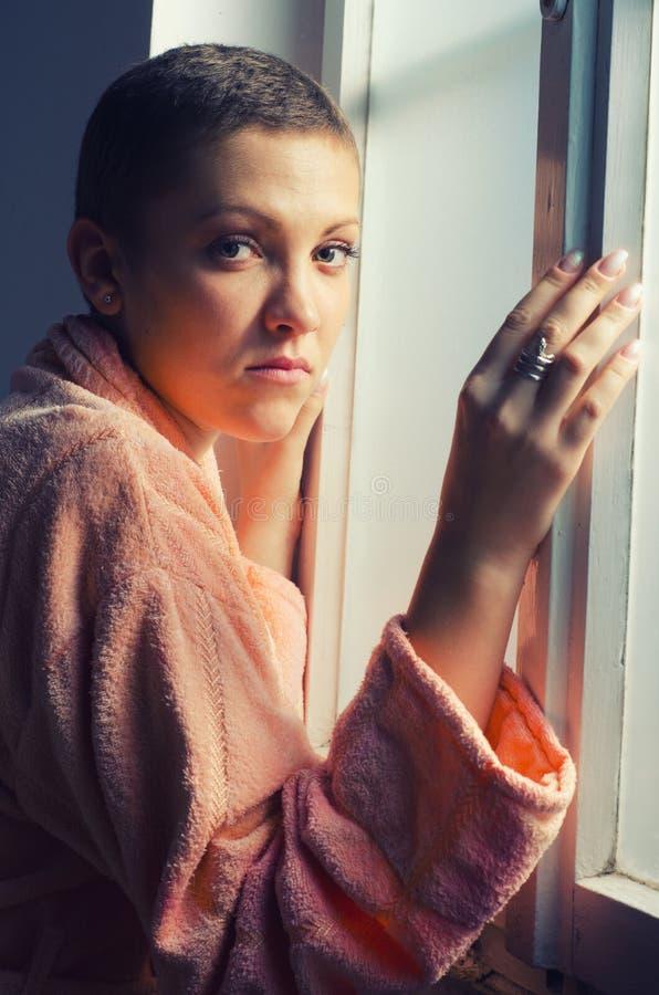 站立在医院窗口旁边的年轻女性癌症患者 库存照片