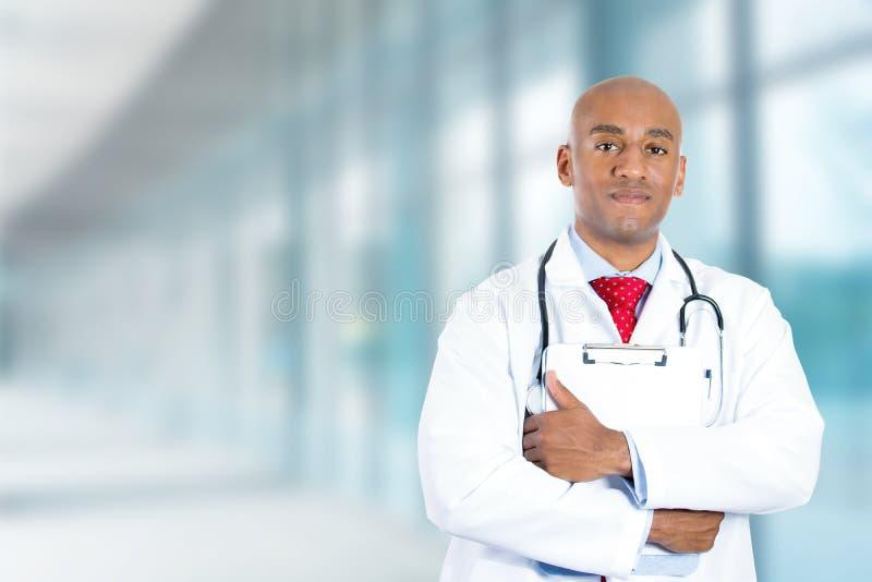 站立在医院走廊的愉快的确信的年轻医生 免版税库存照片