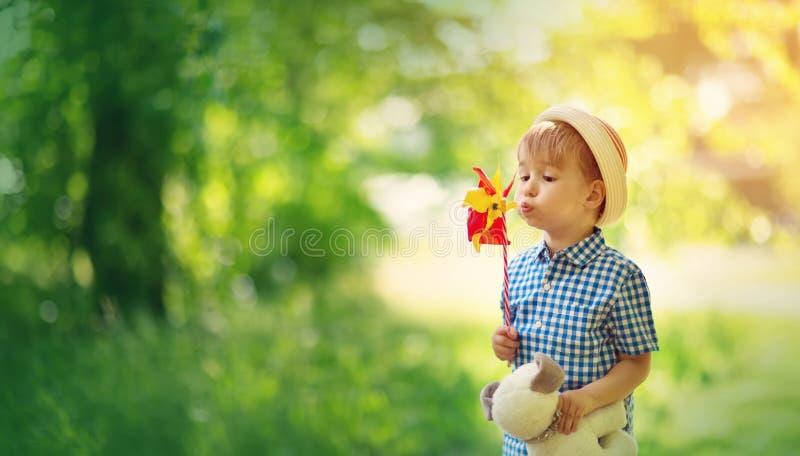 站立在fieald的草的男婴与风车 图库摄影