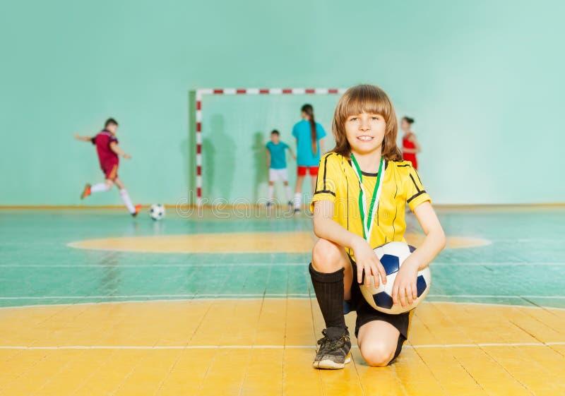 站立在futsal的膝盖的足球队员上尉 免版税库存图片