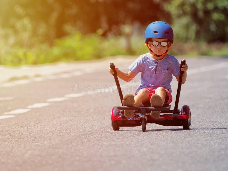 站立在hoverboard或gyroscooter的愉快的男孩与kart通入 免版税库存照片