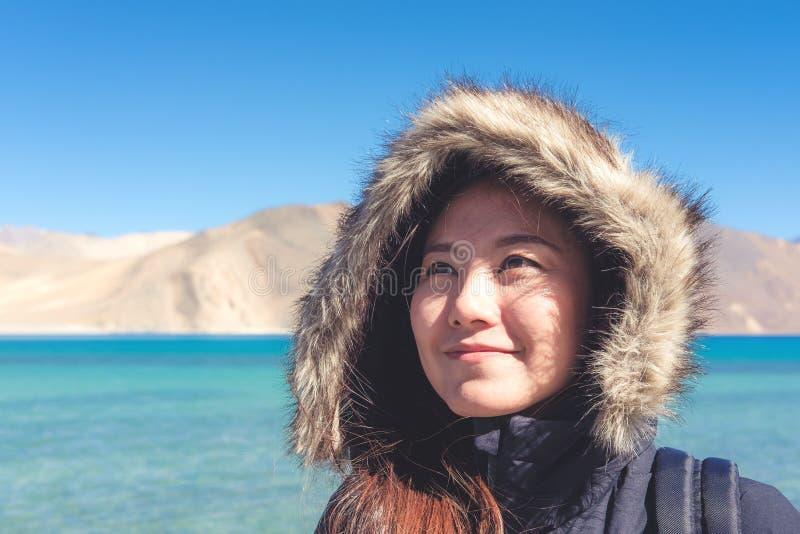 站立在Pangong湖前面的一名美丽的亚裔妇女的画象图象 库存照片
