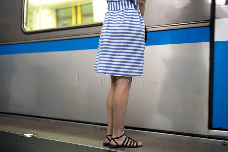 站立在peron的礼服的少妇在通过的火车旁边  库存照片