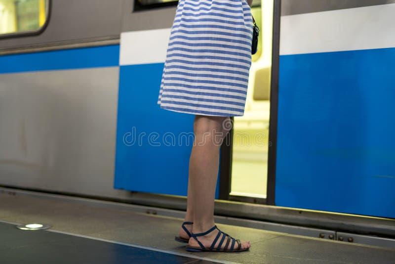 站立在peron的礼服的少妇在通过的火车旁边  库存图片