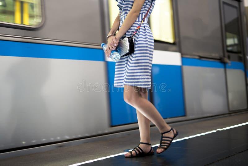 站立在peron的礼服的少妇在通过的火车旁边  免版税库存照片