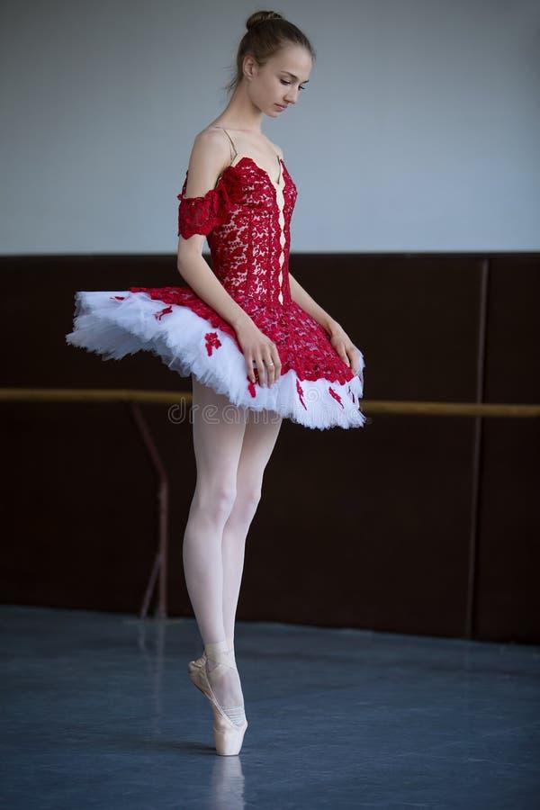 站立在pointe的苗条芭蕾舞女演员在看的舞厅下来 免版税库存图片