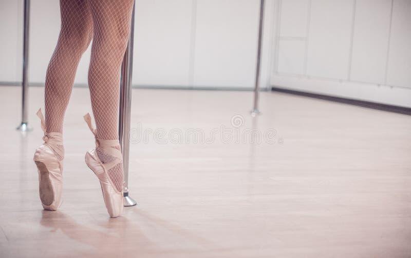 站立在Pointe的跳芭蕾舞者在杆附近在有木地板的空的演播室 特写镜头 免版税库存图片