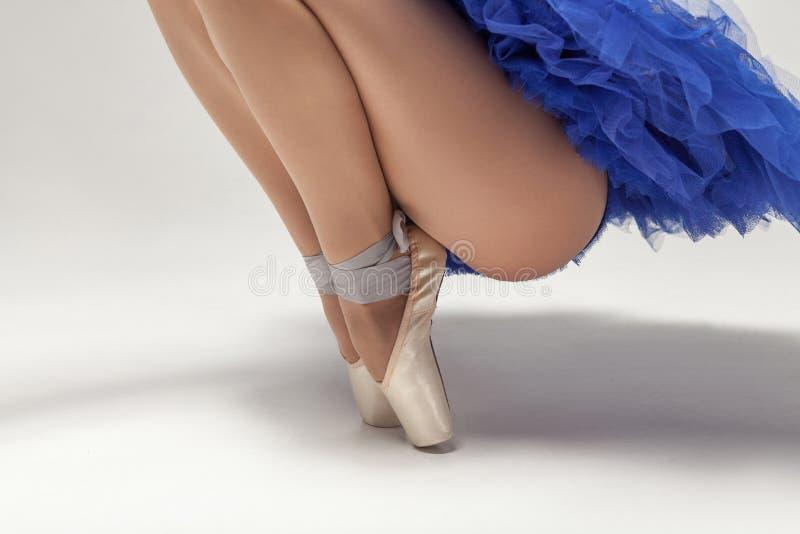 站立在pointe鞋子孤立的脚趾的蓝色礼服的芭蕾舞女演员 免版税图库摄影