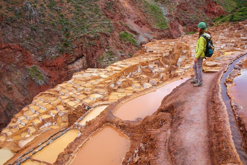 站立在Salinas de Maras盐蒸发的少妇筑成池塘 库存图片
