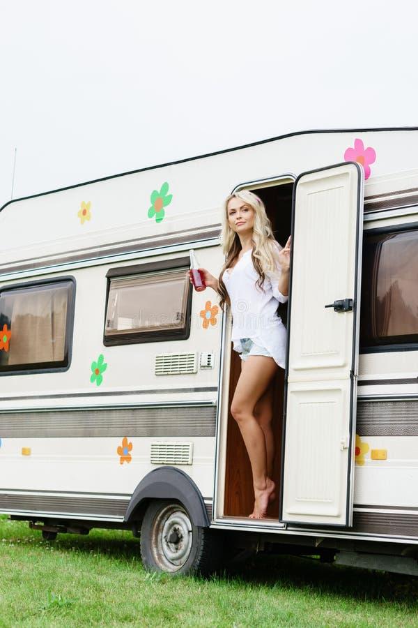 站立在trailer's门的年轻和美丽的嬉皮的女孩 库存照片