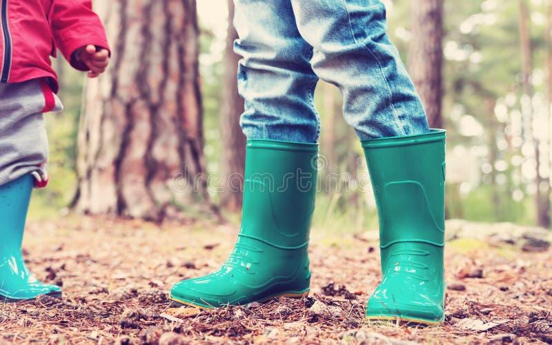 站立在wellies的孩子在森林里 免版税库存图片