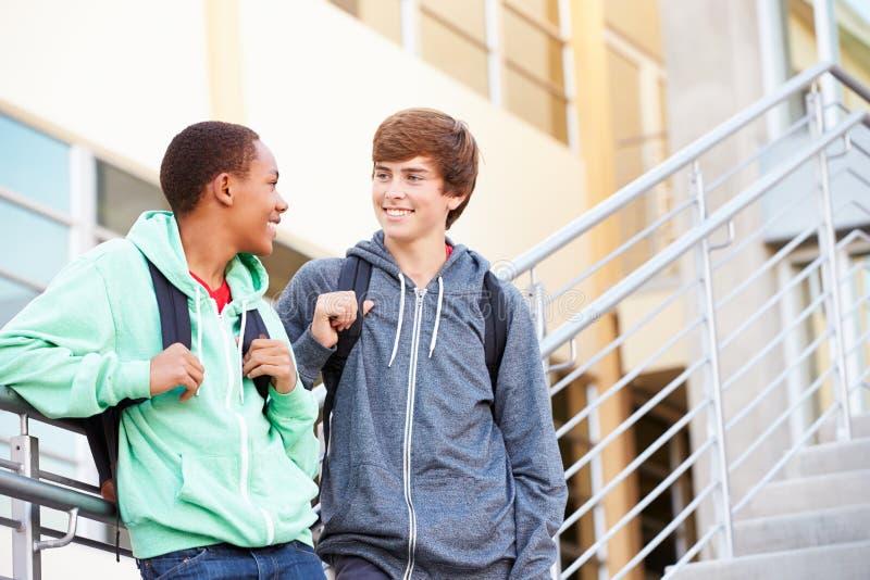 站立外部大厦的两名男性高中学生 图库摄影