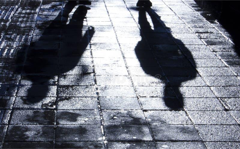 站立夜的两个人模糊的阴影和剪影  免版税库存照片