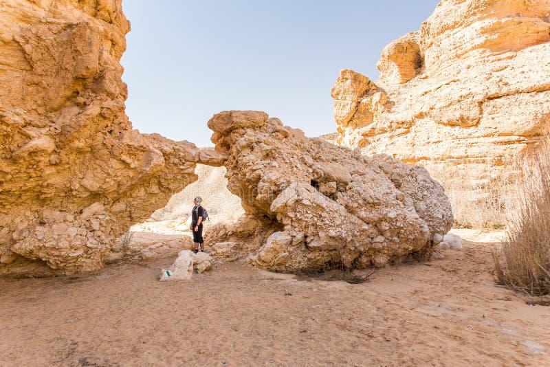 站立大沙漠石头岩石曲拱的旅游背包徒步旅行者 库存图片