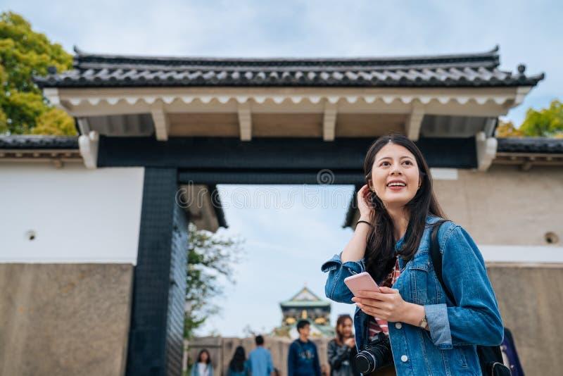 站立大阪城堡的入口的年轻愉快的女孩 典雅的有吸引力的旅客轻打头发和享受看在附近 库存图片