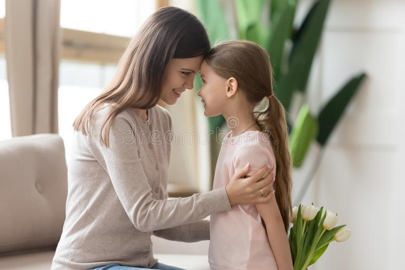 站立女儿掩藏的郁金香接触有母亲的前额 免版税库存照片