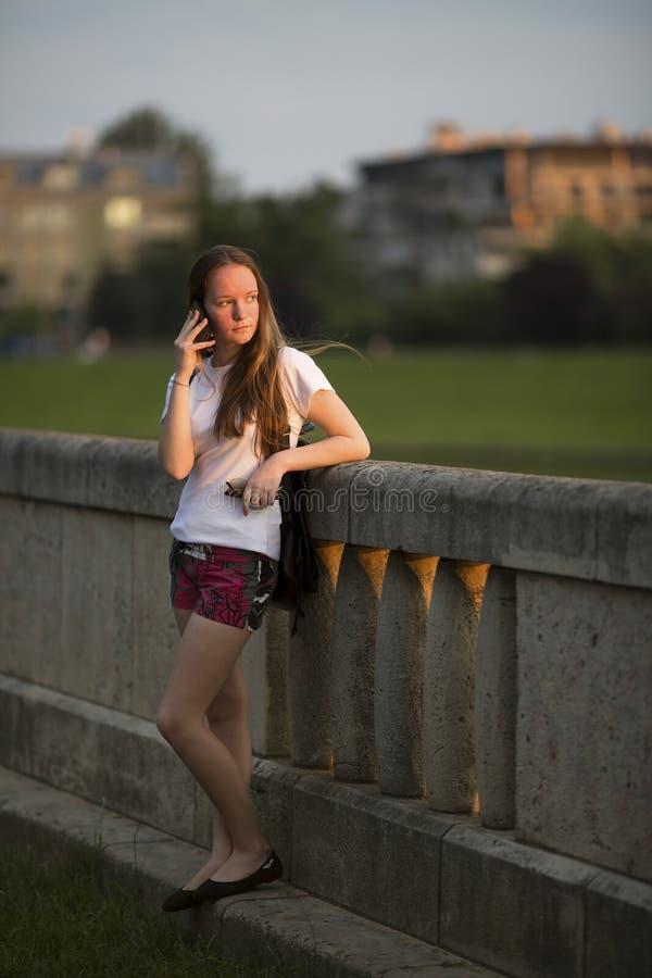站立女孩的少年户外谈话在手机 库存照片