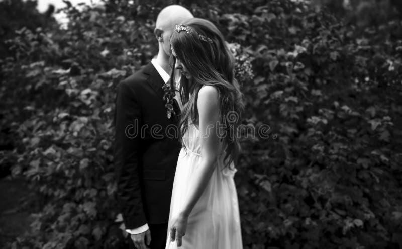 站立婚礼的夫妇的哀伤的图片偏僻在森林里 免版税库存图片