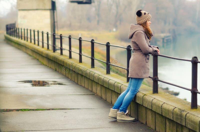 站立孤独的十几岁的女孩室外在冷的冬日 库存照片