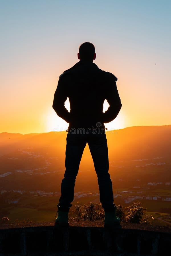 站立孤立的人剪影在与橙色微明的山顶部在从后面的黑暗的平衡的光 免版税库存照片