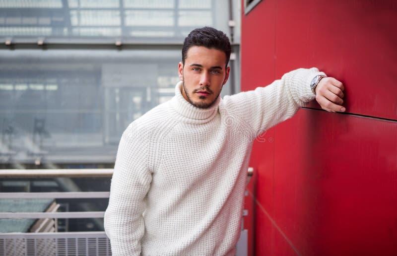 站立室外红色墙壁的时髦的时髦年轻人 免版税库存图片