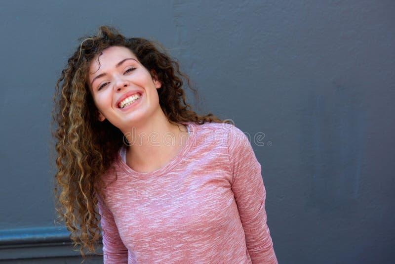 站立对灰色墙壁的笑的青少年的女孩 免版税库存照片