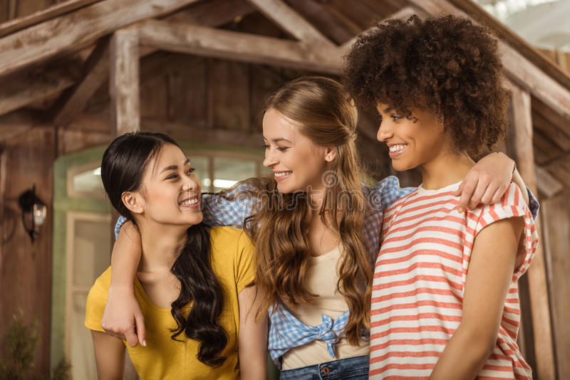 站立小组美丽的微笑的少妇拥抱在门廊 免版税库存照片