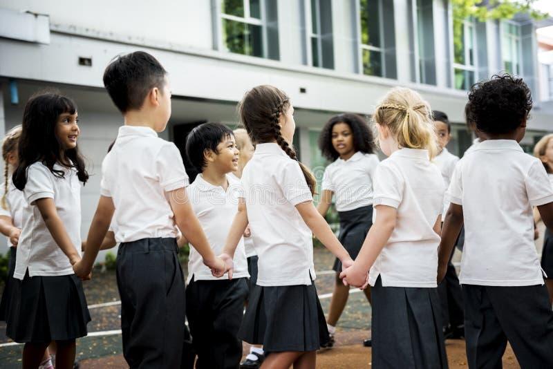站立小组不同的幼儿园的学生握手 库存图片