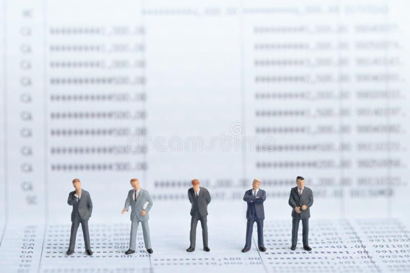 站立小businessmans的形象在银行存款簿的契机 库存图片