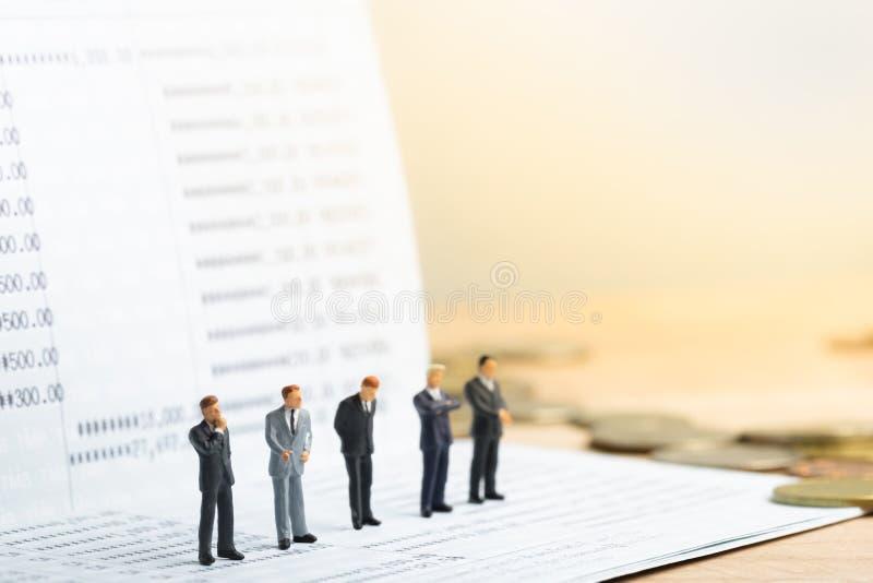 站立小businessmans的形象在银行存款簿的契机 免版税库存图片