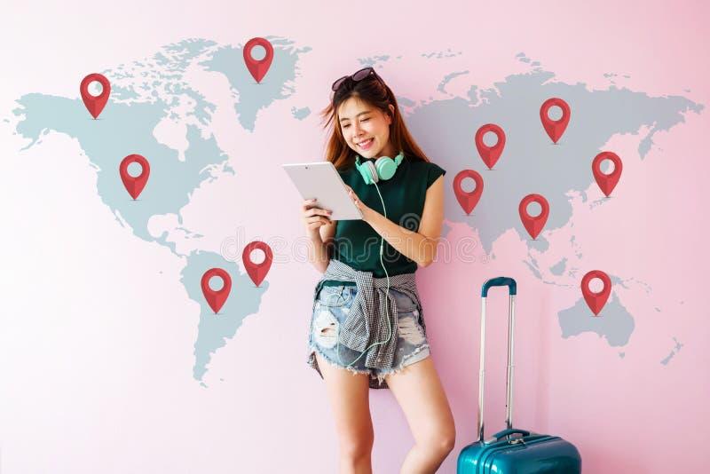 站立带着手提箱和使用Tabl的愉快的年轻旅客妇女 图库摄影