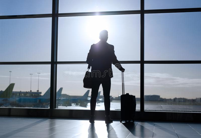 站立带着手提箱的商人在机场 免版税库存照片