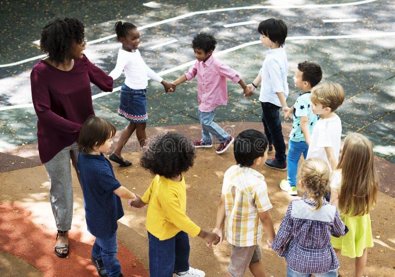 站立幼儿园的学生握在圈子的手形成 免版税图库摄影